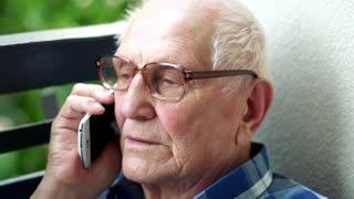 Senior man talking on cellphone on the balcony
