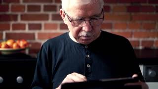 Senior man using tablet while sitting at home