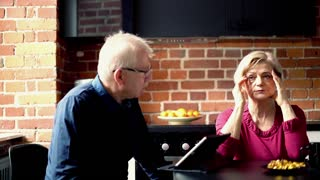 Senior woman having head pain sitting with husband in the kitchen