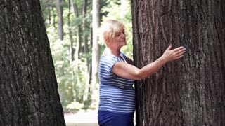 Senior woman hugging tree
