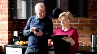 Senior worried couple compare data on tablet and smartphone in the kitchen