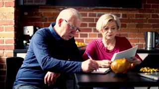 Senior worried couple counting bills sitting in the kitchen