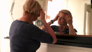 Senior, worried woman checking wrinkles on her face, and applying lipstick in front of the mirror
