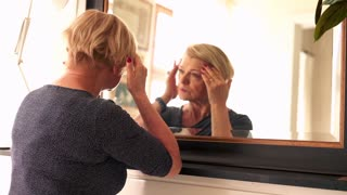 Senior, worried woman checking wrinkles on her face, in front of the mirror