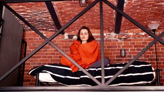 Sick woman in pajamas sitting with blanket in mezzanine bedroom
