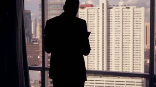 Silhouette of businessman standing with tablet computer by the window in the office, 4K