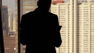 Silhouette of businessman standing with tablet computer by the window in the office