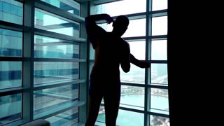 Silhouette of young man dressing up shirt close to the window with splendid city view