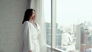 Sleepy, young woman in bathrobe yawning by window with city view, super slow motion