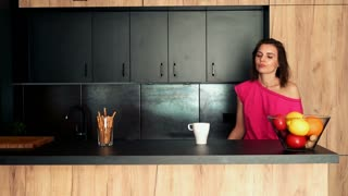 Sleepy, young woman yawning by table in the kitchen