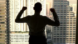 Successful businessman raising arms, power symbol, in the office