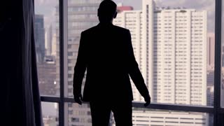 Successful businessman silhouette raising arms, power symbol, in the office, 4K
