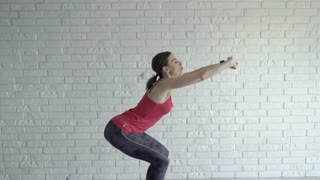 Tired woman taking break and drinking after exercising crouch at home
