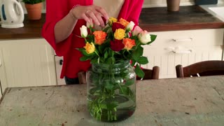 Woman arranging flowers by table, focus on hands
