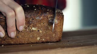 Woman hands slicing wholemeal bread