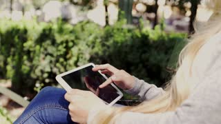 Woman hands using tablet computer sitting in the park