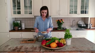 Woman making salad and checking recipe on tablet in the kitchen