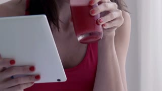 Woman using tablet computer and drink juice, focus on hands