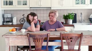 Worried mother comforting her adult daughter in the kitchen.