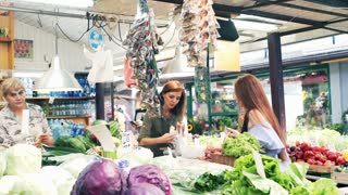 Young, beautiful woman buying fresh vegetables at a local farmer`s market