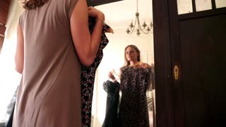 Young, beautiful woman checking new dress in front of the mirror