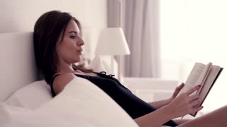 Young, beautiful woman reading book on bed, 4K