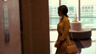 Young beautiful woman waiting for elevator in the hotel, 4K