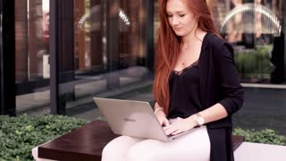 Young beautiful woman with laptop, relaxing on the bench in the city