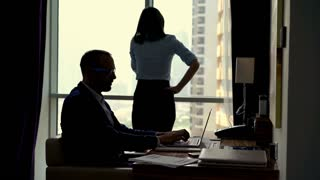 Young business couple working in office with cellphone and laptop int the office, 4K