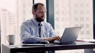 Young businessman having head pain during work on laptop by desk in the office