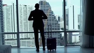 Young businessman with luggage leaving hotel room with splendid view, 240fps