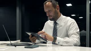 Young businessman with tablet computer sitting by table in the office during night