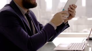 Young businessman with tablet computer sitting by table in the office