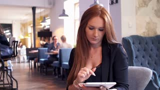 Young businesswoman comparing data on tablet and smartphone while sitting in cafe
