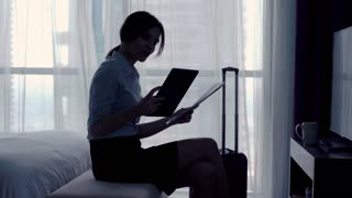 Young businesswoman comparing data on tablet computer and documents on bed at hotel