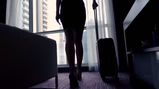 Young businesswoman enter the hotel room with splendid view and looking through the window, super slow motion