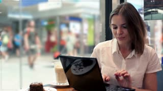 Young businesswoman using modern laptop sitting in cafe