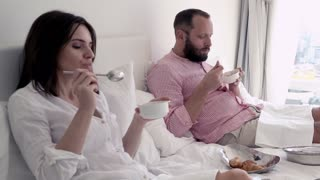 Young couple gets stomach ache during breakfast at bed.