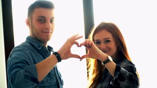 Young couple making heart symbol at their new home