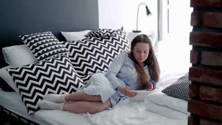 Young, cute woman watching film on tablet on bed