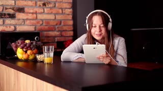 Young cute woman watching movie by table at home