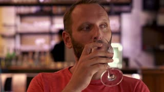 Young, happy man drinking wine in bar on the city