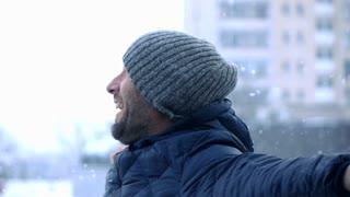 Young, happy man enjoying winter super slow motion