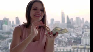 Young, happy  woman counting and  throwing money by window at home, super slow motion