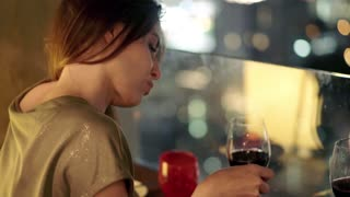 Young impatient woman drinking wine and waiting for someone in rooft bar in the city