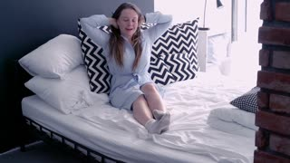Young, lazy woman waking up from nap and stretching arms on bed
