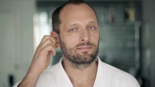 Young man in bathrobe cleaning his ear with cotton bud in bathroom, 4K