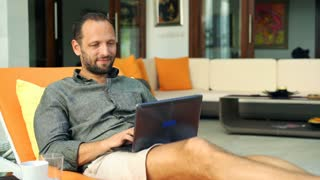 Young man using modern laptop while lying on sunbed at home, 4K