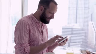 Young man using tablet during breakfast at home
