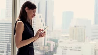Young, pretty businesswoman walking with smartphone by window in the office.
